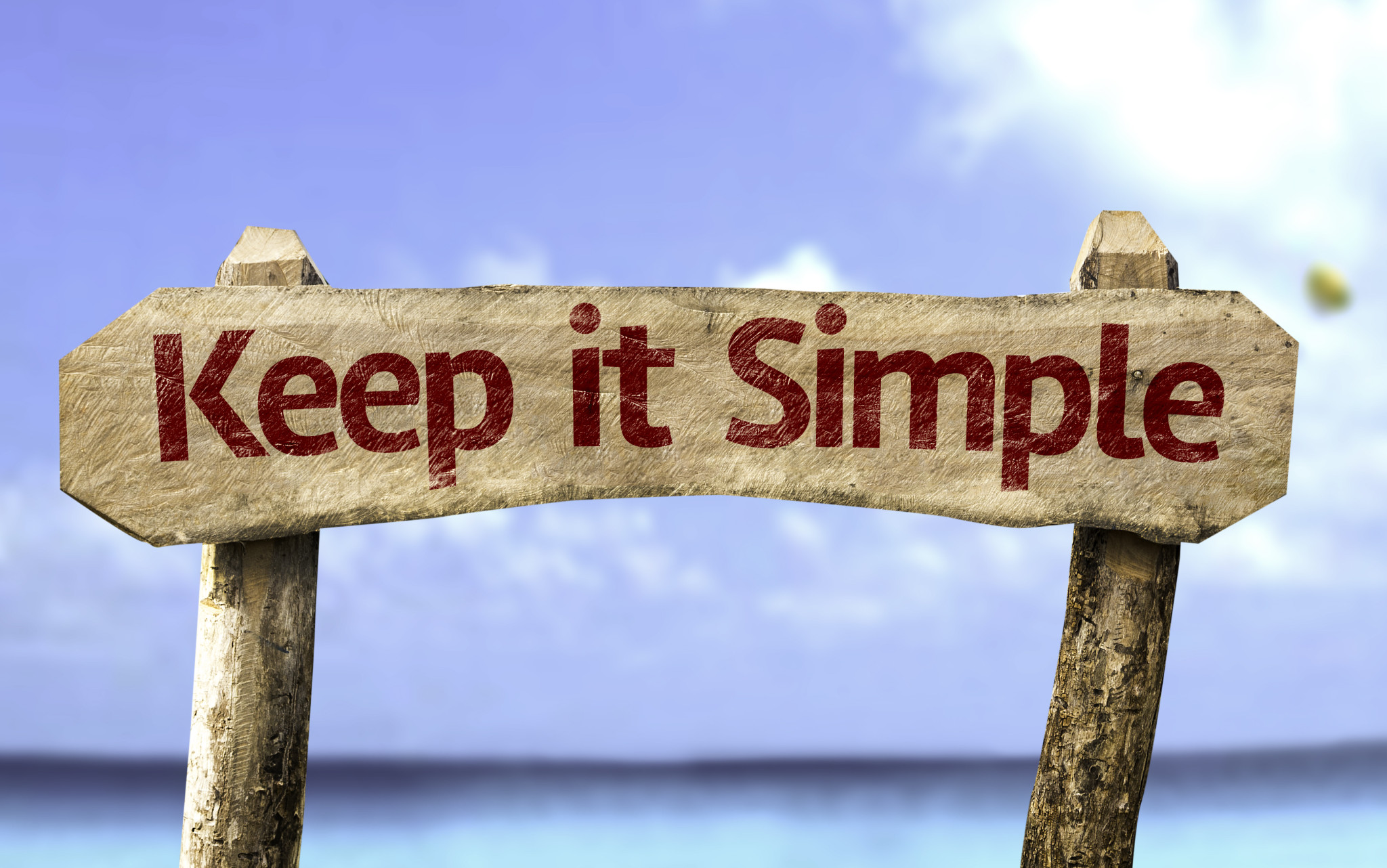 Keep It Simple sign with a beach on background - Werkdrukverlager