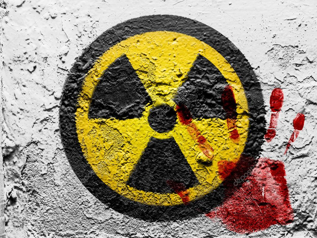 Nuclear radiation symbol painted on grunge wall with bloody palmprint ...