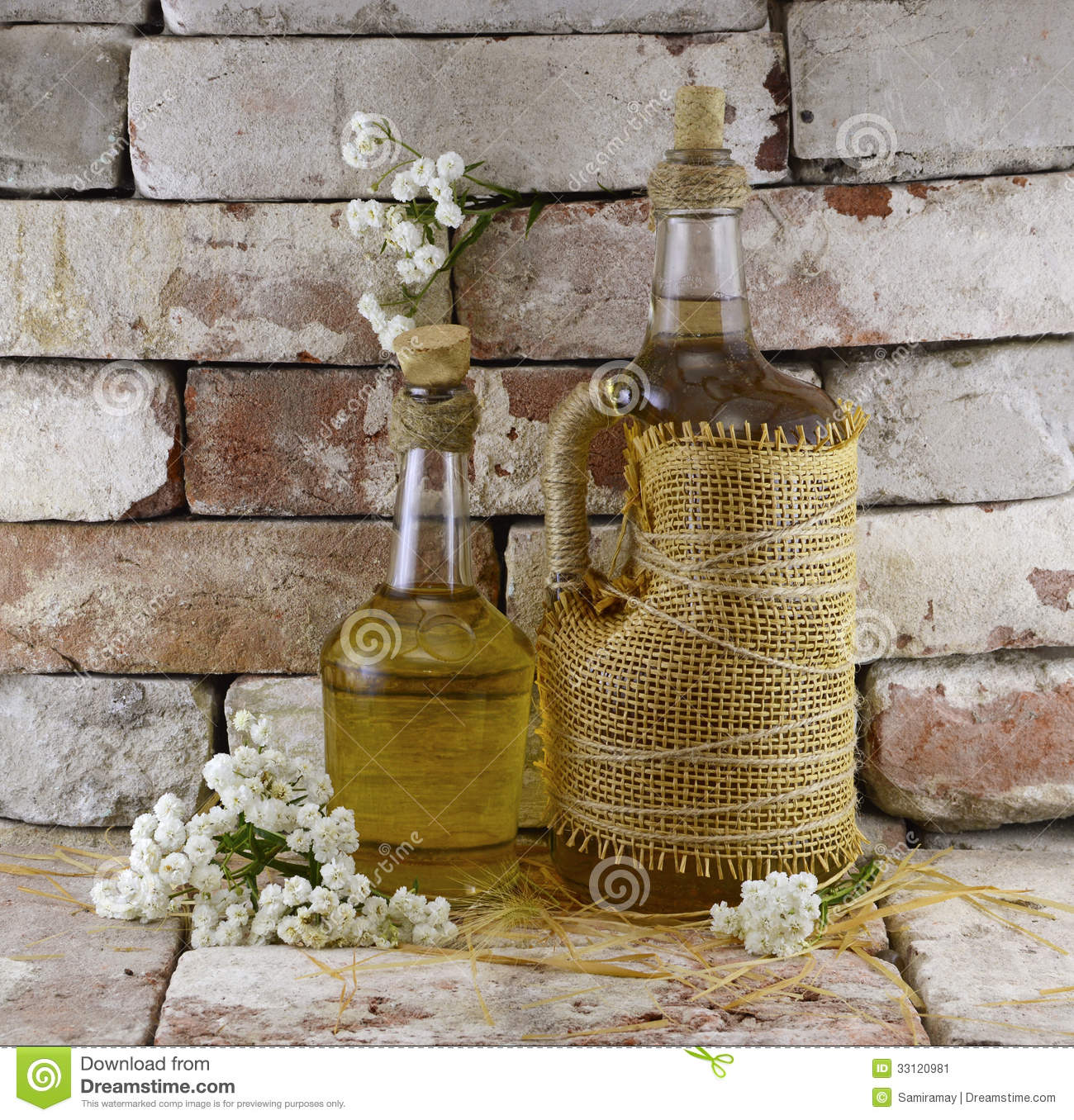 Two bottles of cider with white flowers in cellar background.